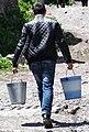 Man Carrying Pails - En Route to Gergeti Trinity Church - Outside Kazbegi - Georgia (18387735818).jpg