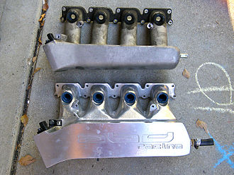 Inlet manifold - Comparison of a stock intake manifold for a Volkswagen 1.8T engine (top) to a custom-built one used in competition (bottom). In the custom-built manifold, the runners to the intake ports on the cylinder head are much wider and more gently tapered. This difference improves the volumetric efficiency of the engine's fuel/air intake.