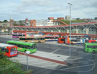 Mansfield - Mansfield bus station with the turf-roof and solar panels of Queen's Place low-energy building visible behind, and part of the old Co-op now known as Beale's to its left