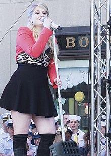 Meghan Trainor singing into a microphone onstage