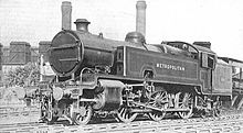 "A black-and-white photograph of a 2-6-4 tank locomotive in three-quarter view. The side tank closest to the camera has the word ""Metropolitan"" painted on it."