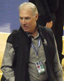 A man in his sixties wearing a press credential around his neck