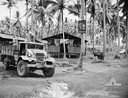 Two shirtless men in the back of a truck, driven (on the right hand side) by a third. In the background are huts on stilts with thatched rooves. The walls are only half height, leaving most of it open to the air.