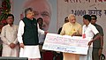 Narendra Modi providing the financial assistance to a local, at Dantewada, in Chattisgarh. The Chief Minister of Chhattisgarh, Dr. Raman Singh, the Minister of State for Mines and Steel, Shri Vishnu Deo Sai are also seen.jpg