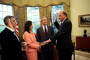 Dina Powell - Powell holding the Bible as John Negroponte is sworn in as Director of National Intelligence in early 2005. Presidential George W. Bush looks on.
