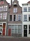 foto van Huis met klokgevel voorzien van half cirkelvormige bekroning met natuurstenen lijst