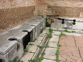 Latrine - Roman public latrine found in the excavations of Ostia Antica; unlike modern installations, the Romans saw no need to provide privacy for individual users.