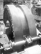A pair of large helical gears in a ship's engine room, mounted herringbone-fashion.