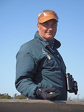 A man wearing binoculars, a brown leather visor, blue jacket, and black gloves stands facing right but with his smiling face towards the camera. He is holding a clicker counter in one hand.