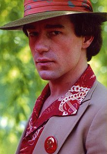 A portrait photo of a man looking side-ways on at the camera with a serious expression on his face. He has a red rimmed hat on, a brown jacket, a gold and red shirt and a button was a man's face on it.