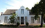 This house displays a harmonious mixture of Cape Dutch and Georgian characteristics. The oldest portion presumably dates from the beginning of the 18th century. The property forms an essential architectural and aesthetic keystone in the historic core of Stellenbosch.