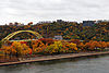 Red, orange, and yellow leaves on trees in an urban park on the shore of a river, a yellow bridge rises in the background