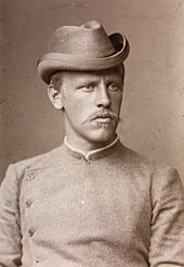 Portrait of a youngish man recognisable as Nansen from the earlier photograph. He has a stern expression and is wearing a collarless jacket buttoned to the neck.