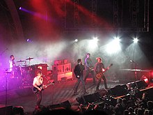 Powderfinger are on stage, with Coghill at left on drums, then Middleton on guitar, Fanning is mid-stage, singing into a microphone, Collins on his bass guitar is next and Haug at extreme right.