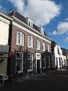 foto van Herenhuis met verdieping ter breedte van vijf vensterassen. Rijk gesneden deur in een omlijsting door pilasters, die een hoofdgestel met snijwerk dragen. Drie stoeppalen