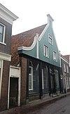 foto van Huis met aan de straat een houten puntgevel met zijpilasters en links een ingezwenkt vleugelstuk
