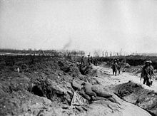 Soldiers march along a sunken dirt road in small groups. Either side of the road debris is strewn and the ground has been churned up from recent artillery attacks