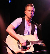 An image of an blonde haired man, wearing a black vest, performing with an acoustic guitar