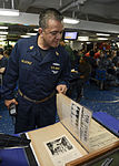 Sailor looks at World War II scrapbook 130604-N-TW634-020.jpg