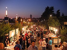 An outdoor book fair at dusk. Vendors are in booths along both sides of a walkway crowded with people.