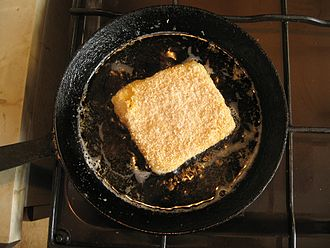 Fried cheese - Smažený sýr being pan-fried in oil