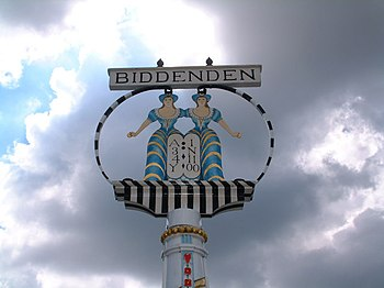 Signpost with the name of Biddenden above a circle enclosing the cut-out and brightly painted figures of two conjoined women