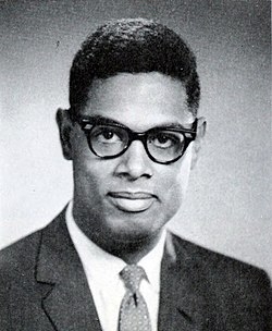 A dark haired man, wearing glasses and a suit and tie, looks into the camera