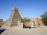 A picture of a very small pyramid with dozens of wooden poles sticking out around it.