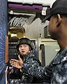 U.S. Navy Air Traffic Controller 2nd Class Morris Carey, background, receives instructions from Master-at-Arms 2nd Class Vonterio Wainwright during a simulated hostage situation aboard the aircraft carrier USS 130130-N-JC752-040.jpg