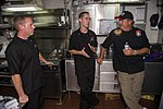 "U.S. Navy Culinary Specialist Seaman Paul Klaras, left, and Culinary Specialist 2nd Class Adam Johnson, center, speak with celebrity chef John Conley during a Navy Entertainment ""Mess Lords"" event aboard 130829-N-LH273-006.jpg"