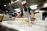 U.S. Navy Culinary Specialist Seaman Timothy Vernon flattens dough as he prepares to make pretzels in the galley of the guided missile destroyer USS Arleigh Burke (DDG 51) March 8, 2014, in Marseille, France 140308-N-WD757-052.jpg