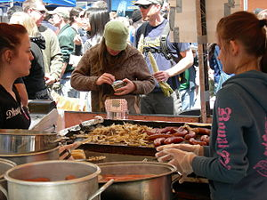 Food booth - Food booth vendors cooking sausages at University District Street Fair, University District, Seattle, Washington.