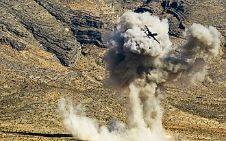 Attack aircraft - A USAF A-10 Thunderbolt II flies past the effects of an AGM-65 Maverick it fired during a close air support training exercise