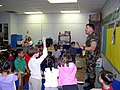 US Navy 030402-N-8005M-001 Chief Builder Joel Baldwin asks a group of 1st, 2nd, and 3rd grade students from Bel Aire Elementary School, what kinds of jobs they think the Seabees are performing while away from home.jpg