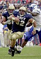US Navy 031004-N-9693M-011 Navy fullback Kyle Eckel outpaces Air Force linebacker Marchello Graddy for yardage.jpg