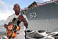 US Navy 041117-N-3228G-002 Musician 2nd Class Rufus Spearman, a guitarist in the Pacific Fleet Band, warms up prior to a tribute ceremony.jpg