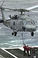 US Navy 050312-N-8119C-011 Crew members aboard USS Nimitz (CVN 68) attach a cargo pendant to an SH-60F Seahawk.jpg