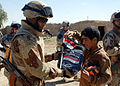 US Navy 060311-N-6901L-089 An Iraqi soldier gives an Iraqi flag and backpack to a local boy during a mission to deliver anti-terrorist leaflets and information to local residents on the outskirts of Taji.jpg