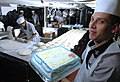 US Navy 060602-N-1332Y-023 Culinary Specialist 3rd Class Hector Melendez assigned aboard the USS Kitty Hawk's (CV 63), displays a cake before serving it to the crew.jpg
