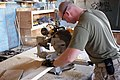 US Navy 070910-M-2819S-013 Hospital Corpsman 3rd Class Jim A. Nettles cuts a piece of wood to fit in a bunker assembly.jpg