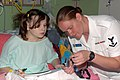 US Navy 080722-N-7975R-001 Personnel Support 3rd Class Jessica White shows a patient at A.I. DuPont Hospital for Children how to attach a Navy lanyard to her cell phone.jpg