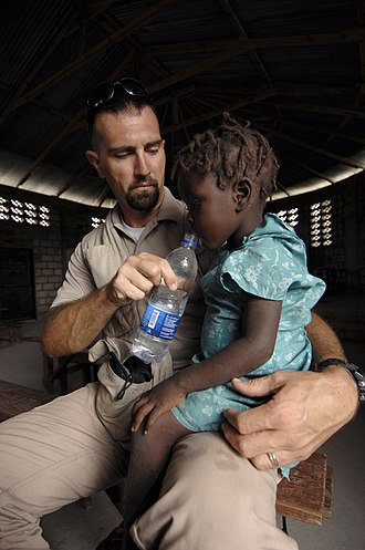 Naval Criminal Investigative Service - An NCIS special agent, assigned to the USS Kearsarge, gives a girl a drink of water during a medical assessment of a local village during hurricane relief operations in Haiti in 2008.