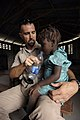 US Navy 080924-N-9620B-009 Naval Criminal Investigative Service Special Agent Jeremy Gouthier, assigned to the amphibious assault ship USS Kearsarge (LHD 3), gives a Haitian girl a drink of water during a medical assessment.jpg