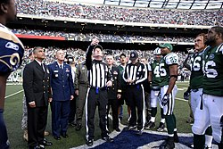 Players and officials looking up at a tossed coin