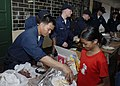 US Navy 090424-N-9520G-181 Aviation Support Equipment Technician 2nd Class Phil Y. Degracia, from Downey, Calif. assigned to the amphibious assault ship USS Essex (LHD 2), serves fruit to students at Banicain Elementary School.jpg