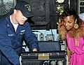 US Navy 100105-N-3666S-008 Fire Controlman 2nd Class Cody Gilbert explains to recording artist and entertainer Ashanti different equipment on the bridge of the guided-missile cruiser USS Port Royal (CG 73).jpg
