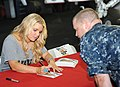 US Navy 101001-N-3793B-071 Jessica Simpson autographs a photo for a Sailor during a USO and Navy Entertainment sponsored visit aboard USS Harry S.jpg