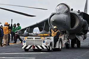 US Navy 120202-N-UM734-022 Sailors maneuvers an AV-8B Harrier on the flight deck of the amphibious assault ship USS Kearsarge (LHD 3).jpg