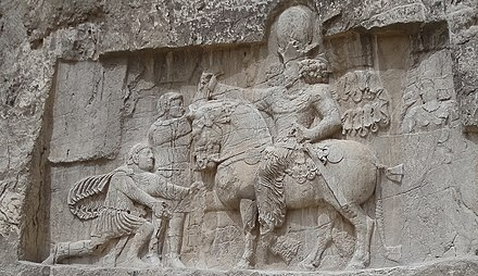 A bas-relief at Naqsh-e Rostam, depicting the victory of Sasanian ruler Shapur I over Roman ruler Valerian Victory of Shapur I over Valerian.jpg