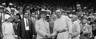 American League - 30th President Calvin Coolidge (1872–1933, served 1923–1929), and Washington Senators pitcher Walter Johnson (1887–1946, played 1907–1927, managed 1929–1932 for Senators; managed Cleveland Indians 1933–1935), shake hands following the Senators' 1924 American League championship at Griffith Stadium, Washington, D.C.